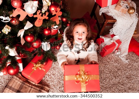 Surprised girl 4-5 year old celebrating christmas. Sitting under christmas tree in room. Looking at camera. Childhood.