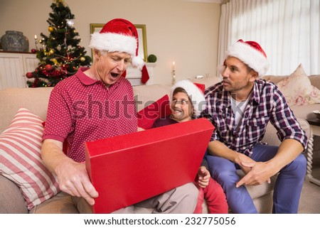Surprised grandfather opening his gift at home in the living room - stock photo