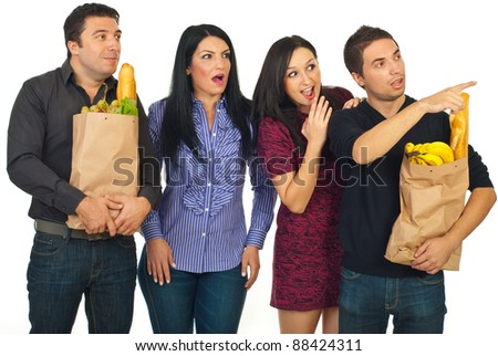 Surprised group of people friends looking away and holding paper bags with food isolated on white background - stock photo