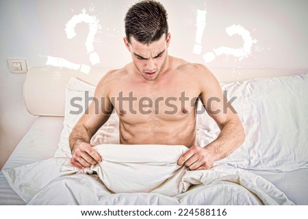surprised half naked young man in bed  looking down at his underwear at his penis under white covers sheet in badroom. Concept photo of male sexuality and man sex problems, domestic atmosphere. - stock photo