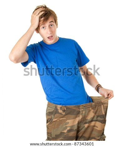 surprised handsome man in too great camouflage trousers, showing how much weight he lost - stock photo