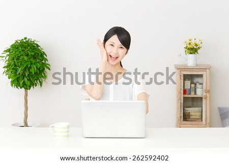 surprised Japanese woman with PC - stock photo