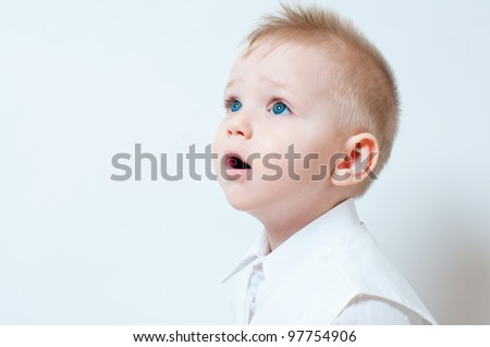 Surprised little boy in a white shirt in studio
