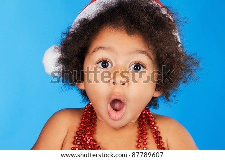 Surprised little child in Christmas hat against blue background - stock photo
