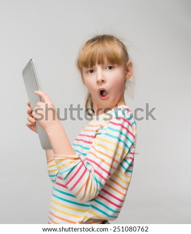 Surprised little girl and her tablet - stock photo
