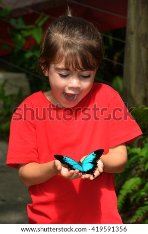 Surprised little girl holds in her hands a Ulysses Swallowtail (Papilio ulysses) is a large swallowtail butterfly of Australasia. This butterfly is used as an emblem for Queensland tourism symbol. - stock photo