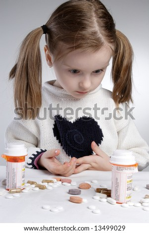 Surprised little girl, looking at pile of medications
