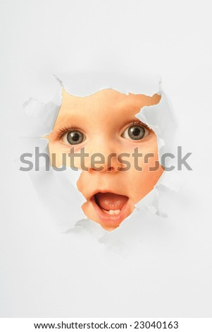 Surprised little girl looking through the torn paper hole