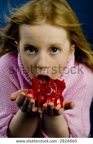 Surprised little girl with candy - stock photo