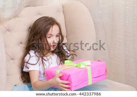 surprised little girl with gift box - stock photo