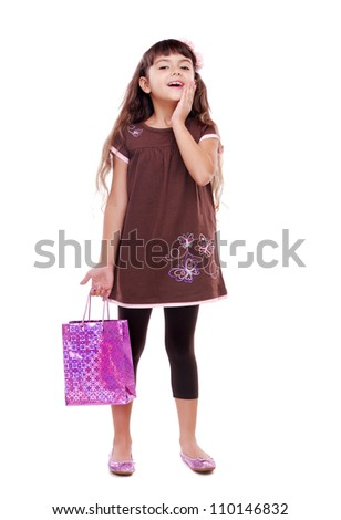 Surprised little girl with paper shopping bag - stock photo