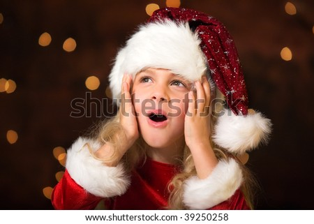 surprised little miss santa, maybe she is seeing santa claus - stock photo