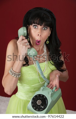 Surprised looking retro-styled woman holding a rotary telephone