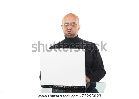 Surprised man blow out his cheeks and looks surprised at the desk with a laptop isolated over white