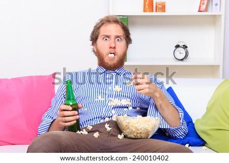 Surprised man eating popcorn on the sofa  - stock photo