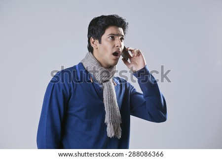 Surprised man having conversation on mobile phone