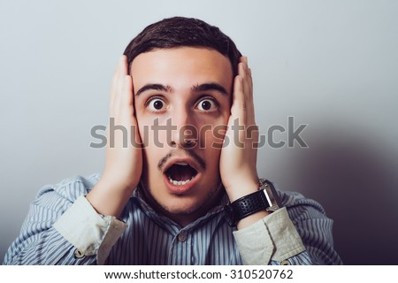 Surprised  man holds his head  - stock photo