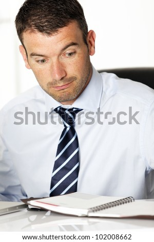 surprised man in office looking at his diary - stock photo