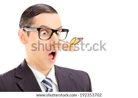 Surprised man with a butterfly on his nose isolated on white background with the focus on the butterfly - stock photo