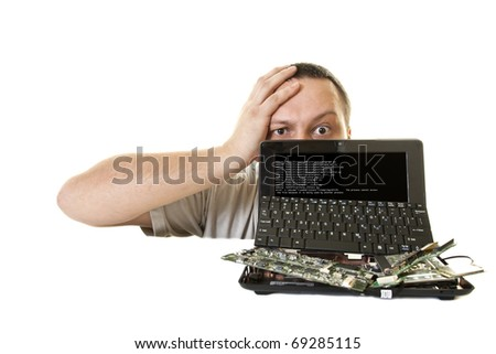 surprised man with a headache in front of destroyed computers - stock photo