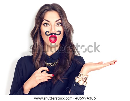 Surprised model Girl holding funny mustache on stick and showing empty copy space on open hand palm for text, white background. Happy girl presenting point. Proposing product. Advertisement gesture - stock photo