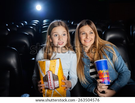 Surprised mother and daughter watching film in movie theater - stock photo