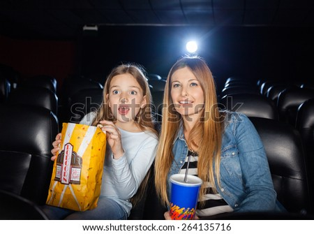 Surprised mother and daughter watching movie in cinema theater - stock photo