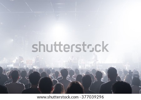 Surprised music band crowds standing illuminated from stage lights. (Very shallow depth of field)