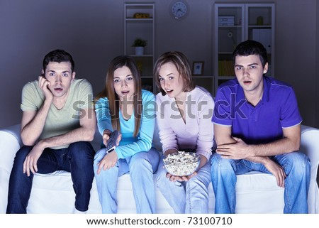 Surprised people are watching a movie - stock photo