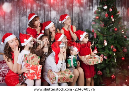 surprised people in santa cluas hats holding presents and looking at Christmas tree - stock photo