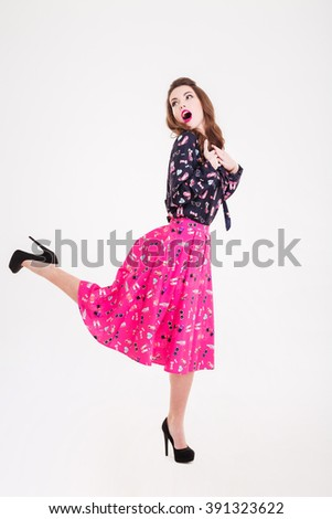 Surprised playful pretty young woman with opened mouth posing over white background  - stock photo