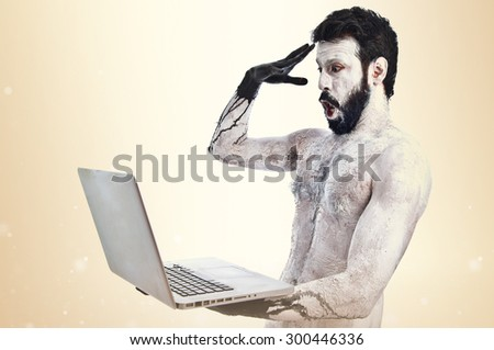 Surprised primitive with laptop over ocher background - stock photo