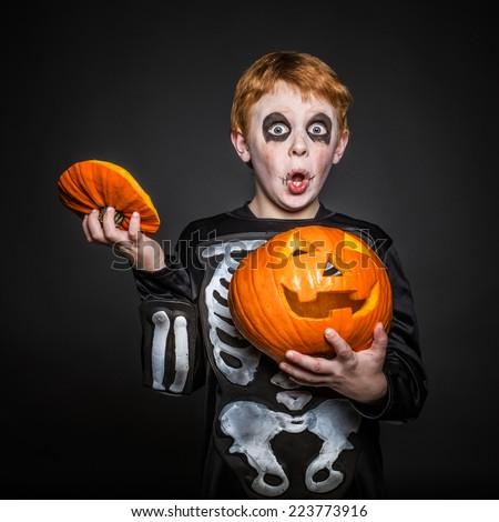 Surprised red haired boy in Halloween costume holding a orange pumpkin. Skeleton. Studio portrait over black background - stock photo