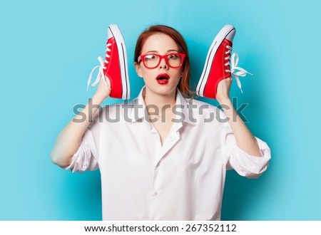 Surprised redhead girl in white shirt with gumshoes on blue background. - stock photo