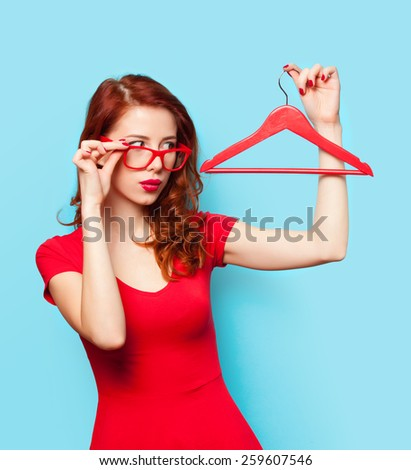 Surprised redhead girl with hanger on blue background. - stock photo