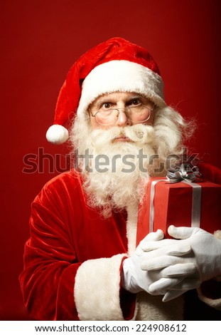 Surprised Santa Claus with red giftbox looking at camera - stock photo