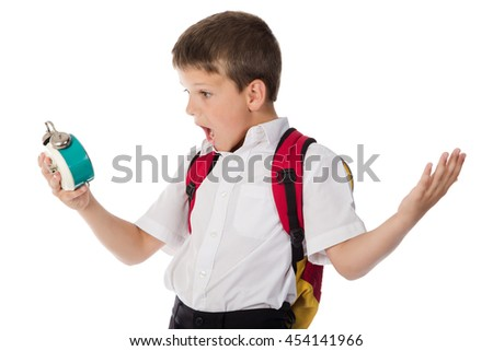 Surprised schoolboy with alarm clock in hand, isolated on white