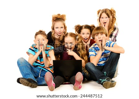 Surprised schoolboys and girls sitting with laptop. Isolated over white. - stock photo