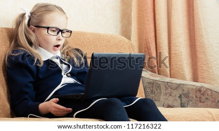 Surprised schoolgirl in glasses with a laptop.