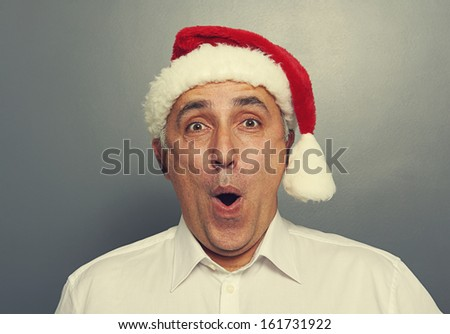 surprised senior man in red christmas hat over grey background