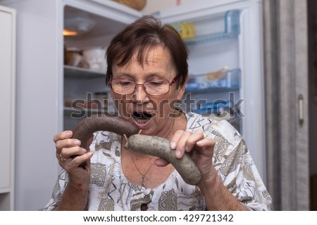 Surprised senior woman holding pork liver sausages while standing in front of the open fridge in the kitchen.