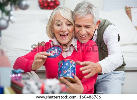 Surprised senior woman with man looking at Christmas gift at home - stock photo