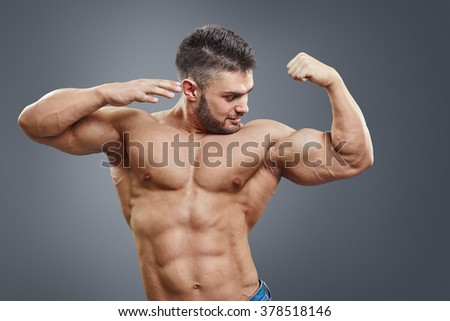 Surprised shirtless muscular man pointing to his strained bicep arm. Bodybuilder gain in bicep.