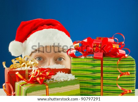 Surprised teen girl looking from behind the Christmas presents - stock photo