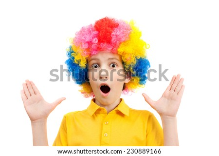 surprised the boy in the bright multi-colored wig - stock photo