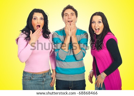 Surprised three people friends standing in a line over yellow background