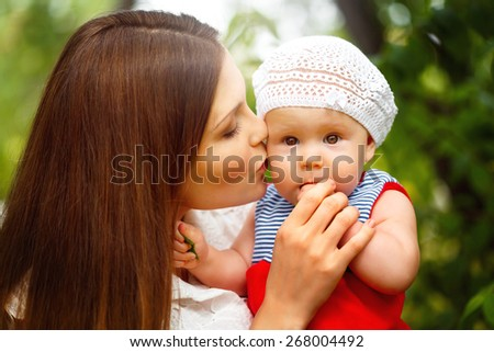 Surprised Toddler Baby Girl sitting on Mom`s Hands, looking into camera. Mother kissing the kid. Relaxing in green summer Park, blurred green background. Close up portrait. Selective focus. - stock photo