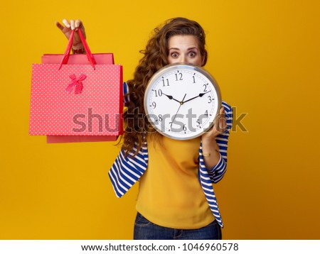 surprised trendy woman with long wavy brunette hair on yellow background hiding behind clock and showing shopping bags
