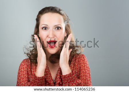 Surprised woman. Beautiful smiling woman in red blouse with open mouth, open palms and red lips. Grey background. Studio shot. - stock photo