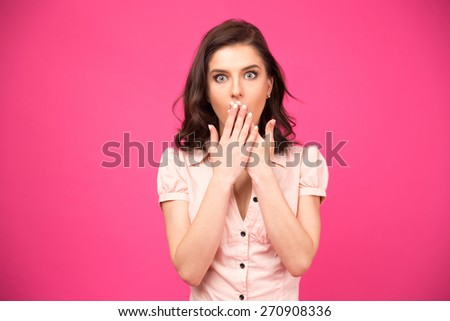 Surprised woman covering her mouth with hands over pink background and looking at camera - stock photo